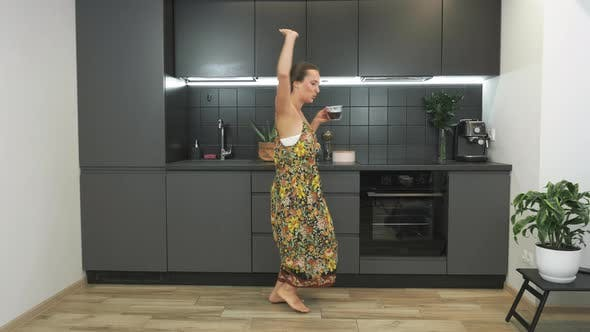 Thumbnail for Young happy girl is dancing in the kitchen, listening to music and drinking coffee in the morning