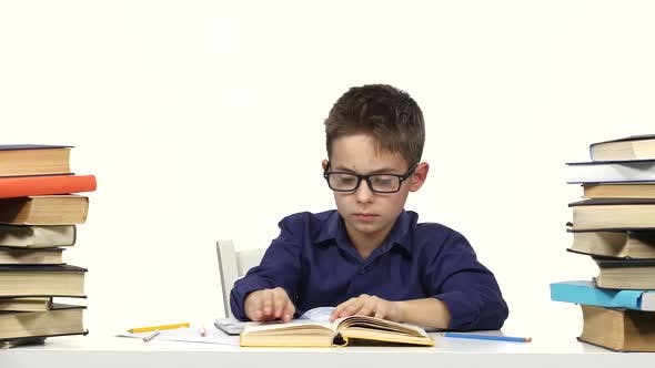 Thumbnail for Little Boy Sits at a Table and Reads the Book Slowly. White Background