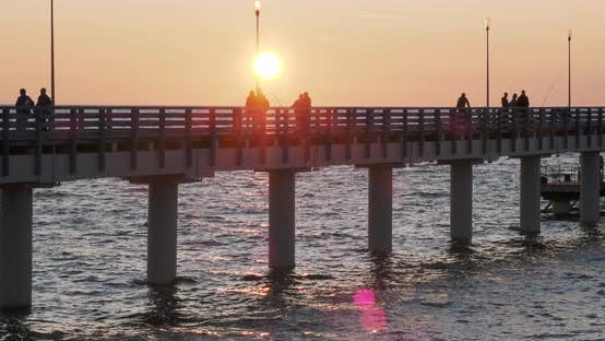 Thumbnail for Silhouettes of People Walking on the Pier Against the Sunset. Local People Are Fishing, Tourists Are