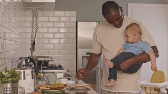 Man Cooking and Holding Baby
