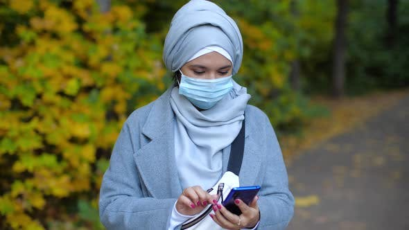 Thumbnail for Young Muslim Woman in Medical Mask with Phone Outdoors at Sunset