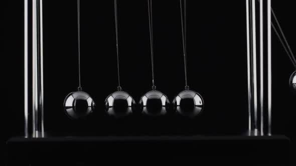 Thumbnail for The balls of a Newtons Cradle colliding in slow motion