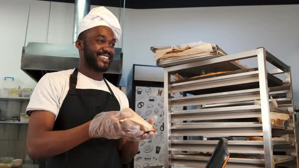 African American Baker in Uniform Sorting Baked Products on Pallets