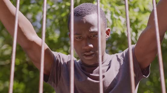 Nahaufnahme Porträt eines jungen verzweifelten Afroamerikaners, der hinter Metallstangen im Freien steht