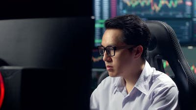 Stock Market Broker Working On Computer With Analyzing Graphs On Multiple Computer Screens