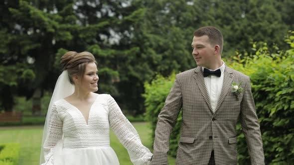 Thumbnail for Jungvermählten. Kaukasischer Bräutigam mit Braut Wandern im Park. Hochzeitspaar. Mann und Frau in der Liebe