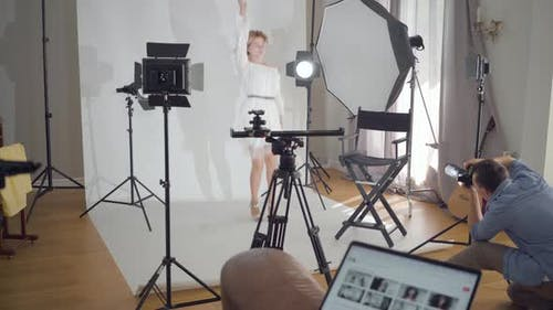 Professional Photographer Taking Photos of Young Female Model Jumping