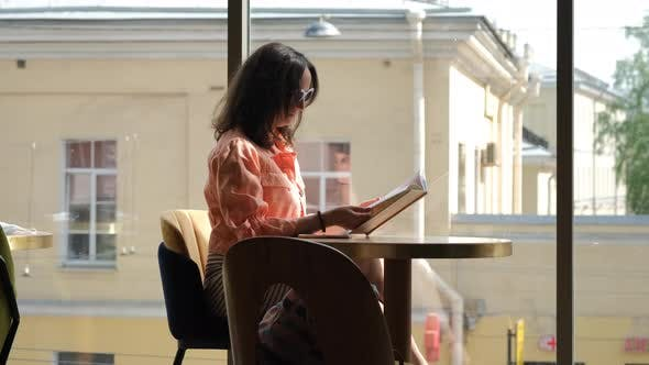 Young Woman Reading Book Indoors in Cafe