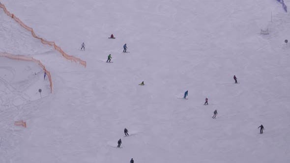 Thumbnail for Skiers and Snowboarders Ride on a Snowy Slope at a Ski Resort in Sunny Day
