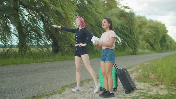 Thumbnail for Women Travelers Hitchhiking with Cardboard Sign