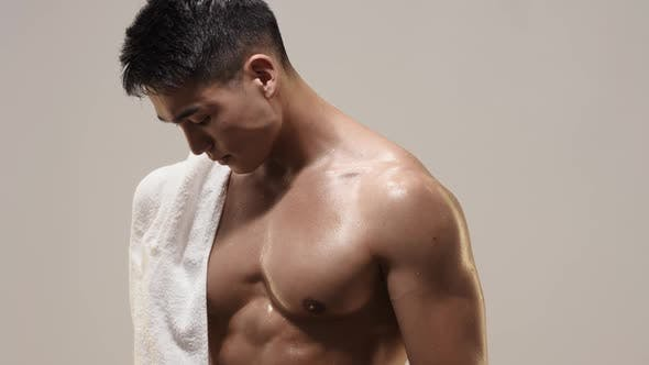 Thumbnail for Tired Muscular Asian Man Indoors Against Gray Background