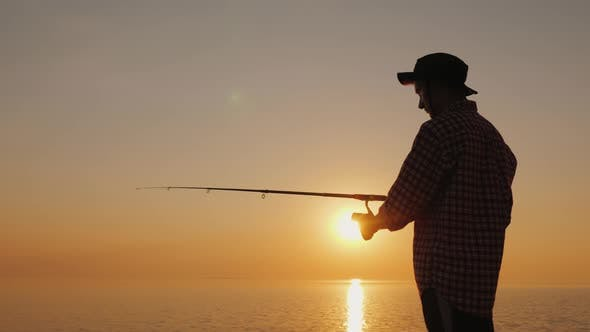 Thumbnail for Silhouette of a Young Fisherman Fishing on the Beach at Sunset. Side View