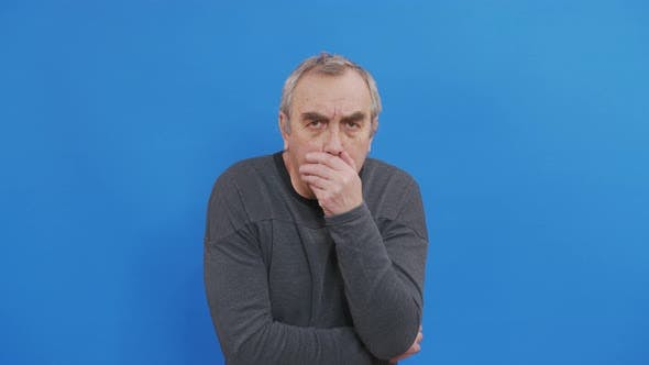 Portrait of Senior Caucasian Man Coughing or Sneezing Into His Arm in Slow Motion
