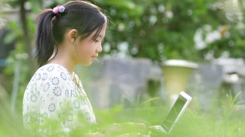 Beautiful Asian Girl  Sitting In Park On The Green Grass With Laptop