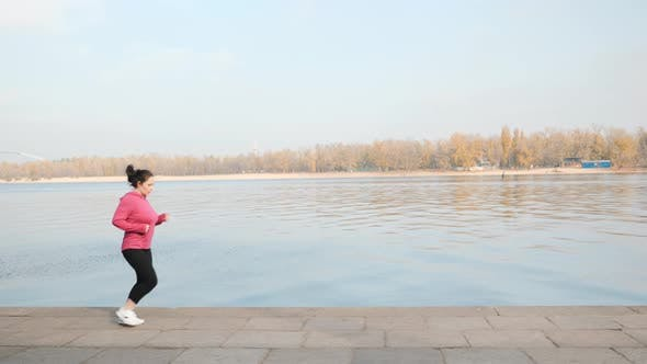 Thumbnail for Young motivated female doing an easy jogging along industrial city river while training for marathon