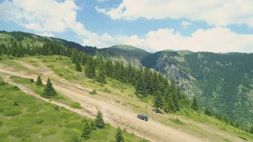 Aerial View Tracking Blue Vehicle Hill Climbing Dirt Road in the Hills