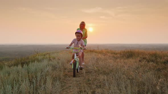 Cover Image for Mom Teaches Daughter To Ride a Bike. The First Success of Children