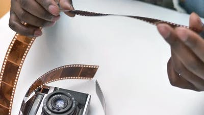 Smiling African American Guy Looks at Photographic Film