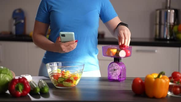 Losing Weight Female Counting Calories in Kitchen