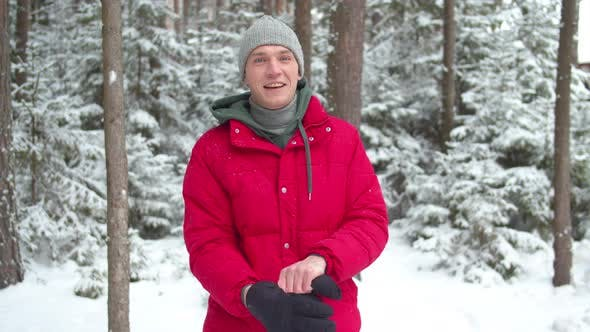 Thumbnail for A Man in a Snowy Forest Puts on Winter Gloves