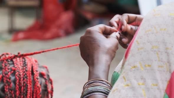 African Woman Weaving African Braids with Red Kanekalon Outdoor Zanzibar Africa