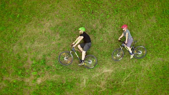 Thumbnail for Aerial view of cyclists lying down on the grass with their bicycles in Slovenia.