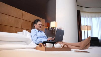 Businesswoman Working on Laptop in Hotel Room