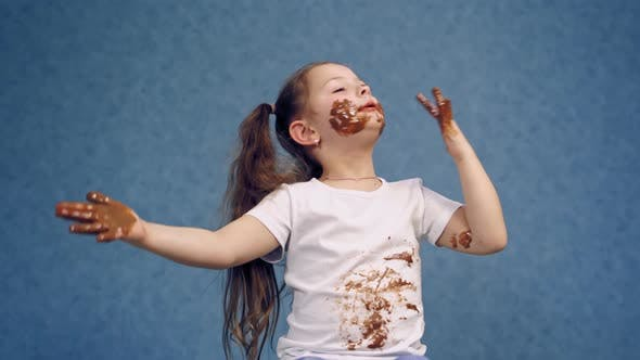 Thumbnail for Cheerful little girl licking chocolate from her fingers