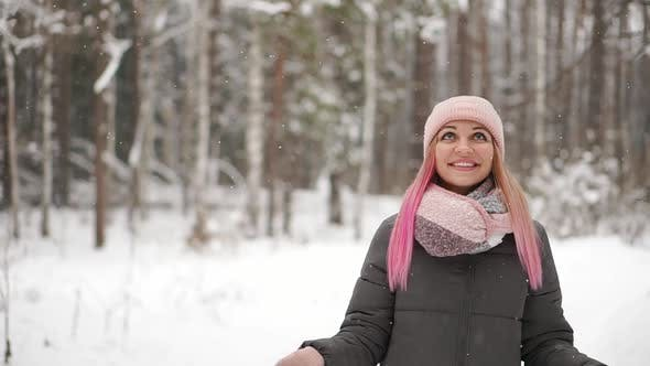 Thumbnail for Woman in a Jacket and Hat in Slow Motion Looks at the Snow and Catches Snowflakes Smiling