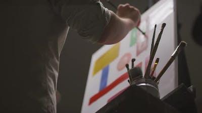 Painter Creating Artwork In Dark Studio