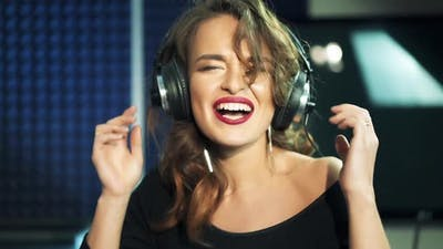 Professional recording studio. Girl in the headphones sings. Close-up