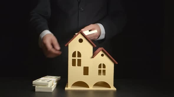 Businessman counts a money and throws it on a table near a house model