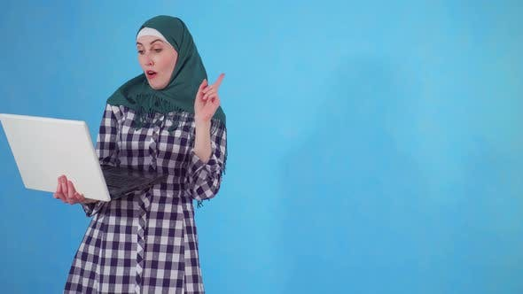 Thoughtful Young Muslim Woman Finds a Solution and Uses a Laptop on a Blue Background