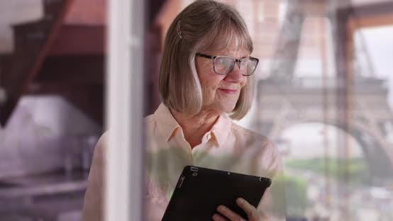 Mature lady using pad device indoors with Eiffel Tower reflection on window