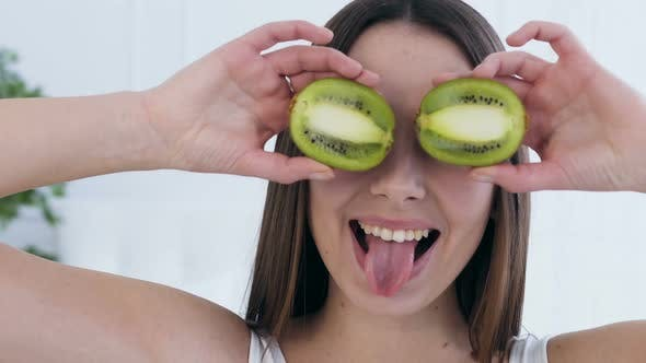 Thumbnail for Attractive Happy Woman Posing with Kiwi on Eyes