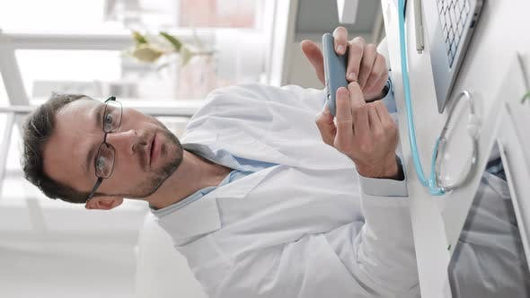 Doctor Using Smartphone at Workplace