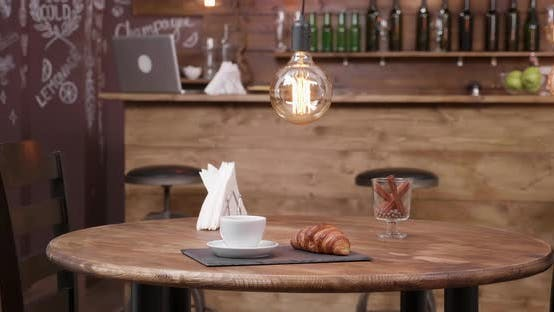 Thumbnail for Minimalist Composition of a Cup of Coffee and a Croissant on a Dark Tray