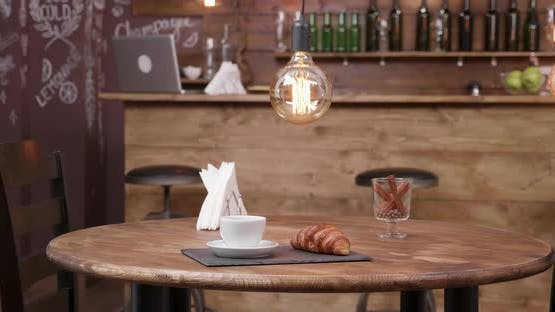 Minimalist Composition of a Cup of Coffee and a Croissant on a Dark Tray