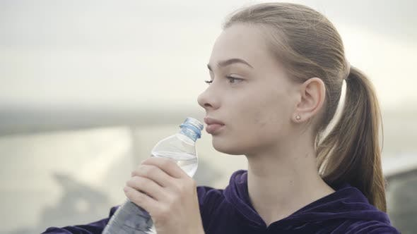 Closeup Face of Confident Slim Beautiful Sportswoman Drinking Refreshing Water Outdoors at the