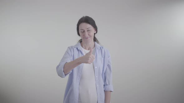 Thumbnail for Adult Brunette Woman Showing Thumb Up and Gesturing Yes By Shaking Head. Portrait of Smiling