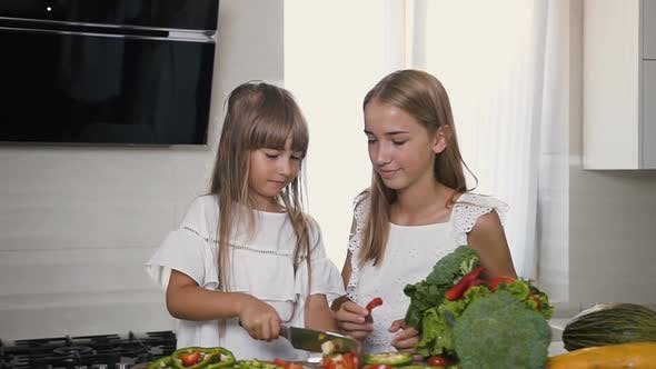 Thumbnail for Two Attractive Girls with Long Hair in white Dresses Cutting a Vegetables Slicing
