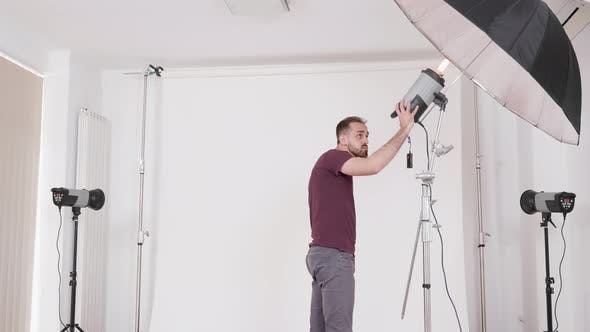 Thumbnail for Medium Shot of a Photographer in a Studio Setting Up the Equipment