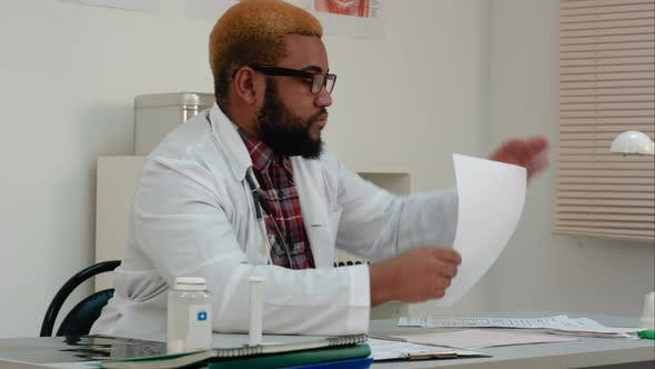 Thumbnail for Afroamerican Physician Working with Medical Forms and Papers in Hospital Office Room