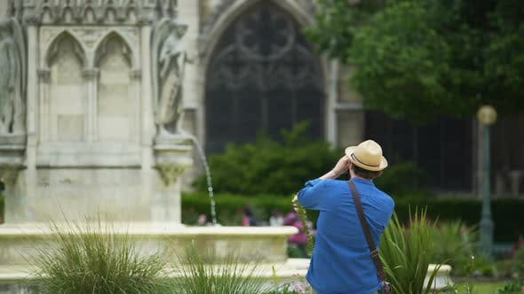 Interested Male Tourist Taking a Photo of Fountain and Notre-Dame De Paris