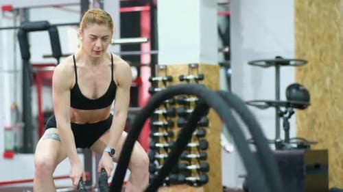 Sportswoman Working Out in Functional Training Gym Doing Exercise with Battle Ropes