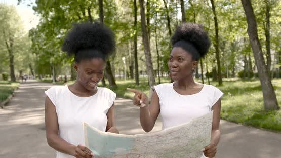 African Female Friends with a Map in Park