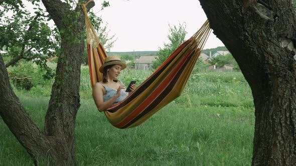 Cute woman in hat and earphones listening to music, singing the song and using mobile in hammock