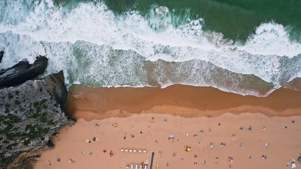 Thumbnail for Aerial Bird Eye View of Praia Da Adraga Beach. Huge Waves Rolling Towards the Beach. Atlantic Ocean