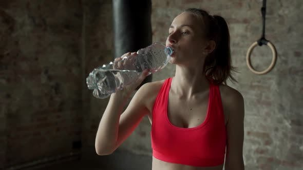 Woman Drinking Water in Gym After Workout
