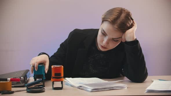 Thumbnail for Tired Girl Is Putting Two Stamps on Documents and Throwing Them Away